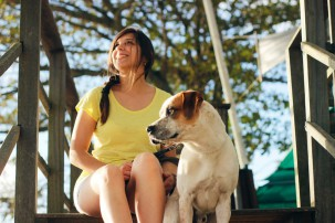 woman sitting with dog, responsible pet owner