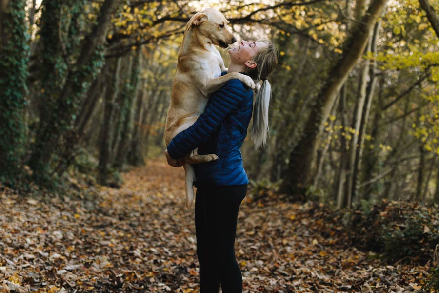 best pet sitter, woman holding dog in arms outdoors