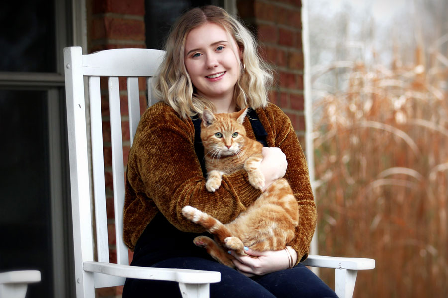 woman sat outdoors holding ginger cat
