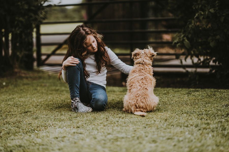 young girl sat outside next to pet dog